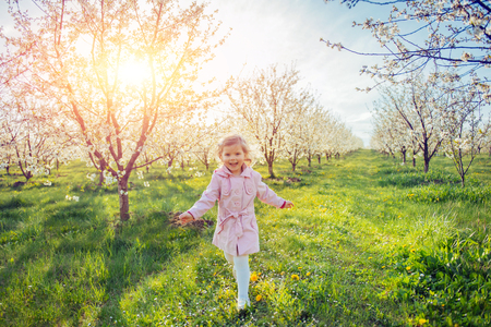 Little baby girl that runs between flowering trees at sunset. Ar Stock Photo