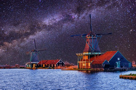 Starry sky over Dutch windmills from the canal in Rotterdam
