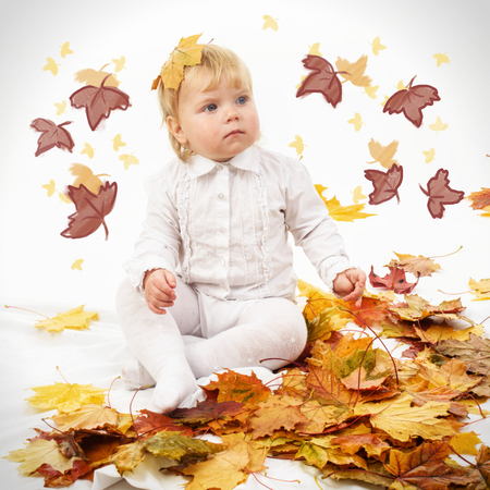 Cute child playing th autumn leaves Stock fotó