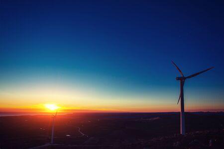 Solar wind turbines at sunset.
