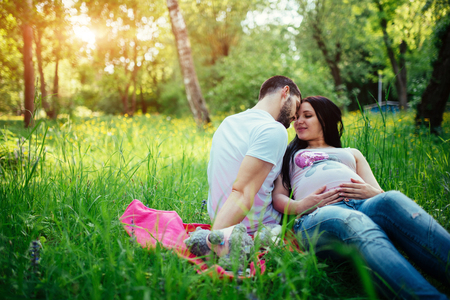 Pregnant woman and her husband relaxing on nature