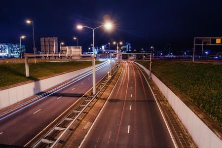 Asphalt road is lit at night.