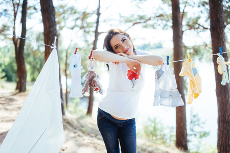 woman hanging baby clothes in linen rope outdoors