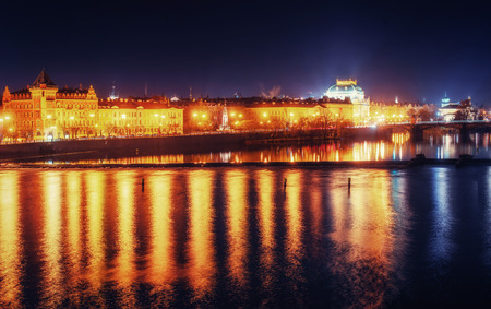 Reflection of Prague caste and the Charles bridge at dusk.
