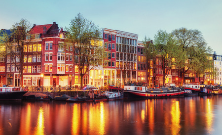 Canal houses of Amsterdam at dusk with vibrant reflections