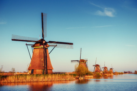 dutch: Colorful spring day with traditional Dutch windmills canal
