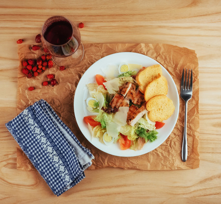 Caesar salad with croutons, quail eggs, cherry tomatoes and gril Stock Photo