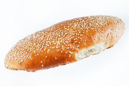 bun sprinkled with sesame seeds on a light background. insulatio