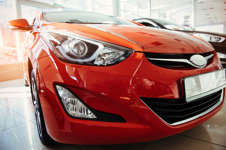 Headlights and hood of sport red car.