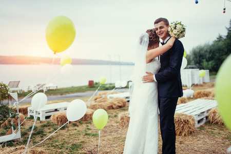 beautiful young wedding couple kissing , blonde bride with flowe
