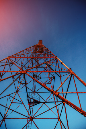 High metal tower on blue sky. Large scale.