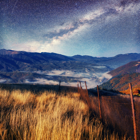 Fantastic starry sky and majestic mountains in the mist. Dramati