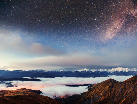 Starry sky above the thick fog on the mountain