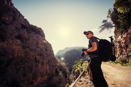 Nature photographer taking photos in the mountains Stock Photo