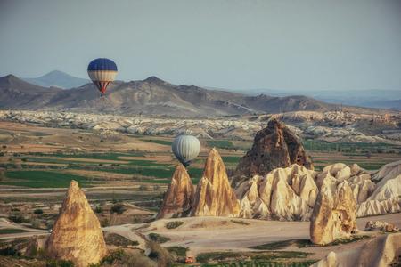 Hot air balloon flying over rock landscape at Cappadocia Turkey. Stock Photo