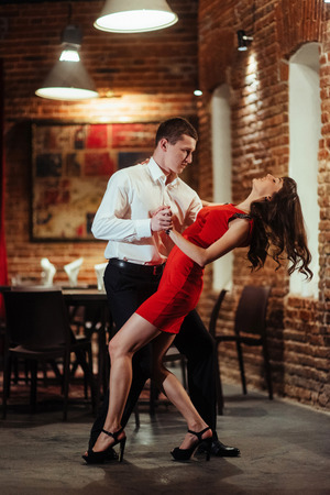 Dancing young couple on a white background. Passionate salsa. Stock Photo