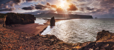 The black sand beach and mountains Reynisfjara Reynisfyal from Cape at sunset in Iceland.