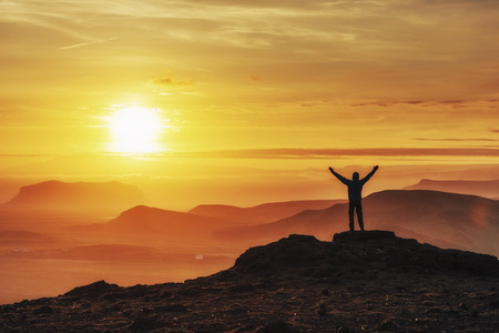Happy man standing on a cliff at sunset. Banque d'images