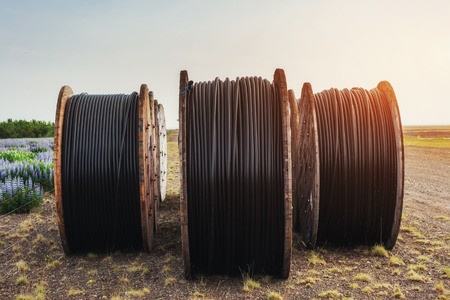 Large rolls of black wires against the blue sky at sunset Imagens