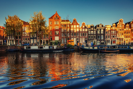 Fantastic sunset that shines on buildings and reflected in the water. Amsterdam is the capital and most populous city in Netherlands. Stock Photo