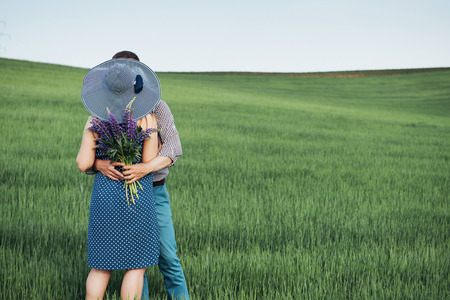 Happy family hugging in a field of green wheat