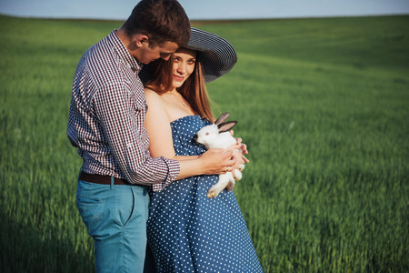 pregnant woman with her husband and rabbit Imagens