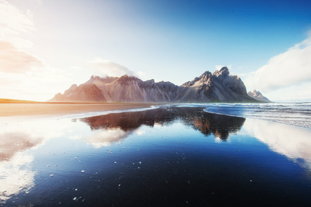 Amazing mountains reflected in the water at sunset. Stoksnes, Ic Stock Photo