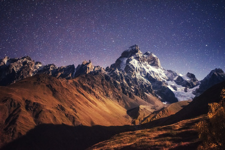 caucas: Fantastic starry sky. Autumn landscape and snow-capped peaks Stock Photo