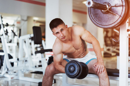 Portrait of a beautiful athletic guy muscles with weights