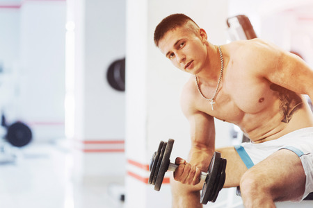 execute: Beautiful athletic bodybuilder guy, carries out exercises with d