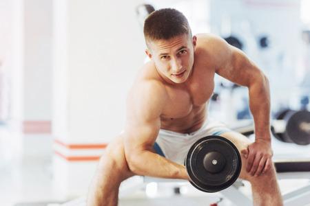 Schöner athletischer Bodybuilderkerl, führt Übungen mit d durch