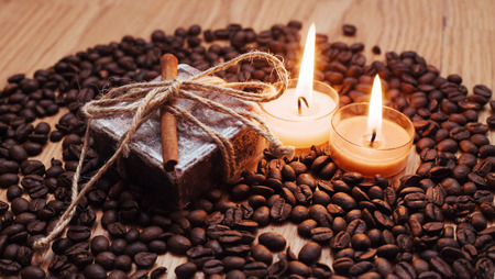 Burning aromatic coffee candle and beans, close-up
