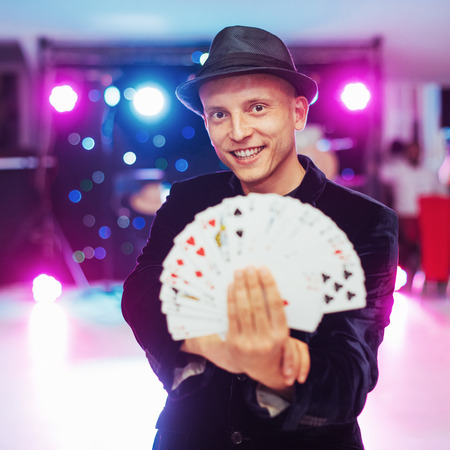 Magician showing trick with playing cards. Magic, circus