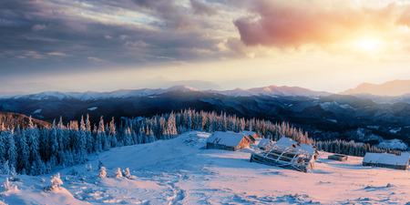 Fantastic sunset over snow-capped mountains and wooden chalets.