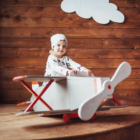 kid playing with wooden airplane