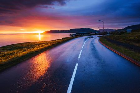 Asphalt road along the sea at sunset Iceland Imagens