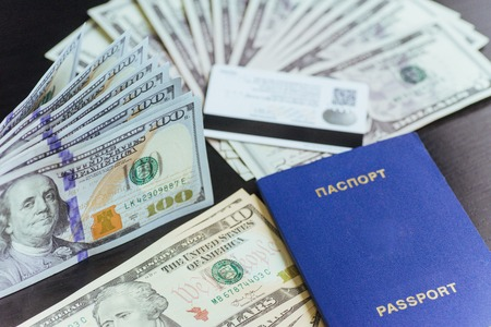 Top view of passport with dollar banknotes on wooden desktop