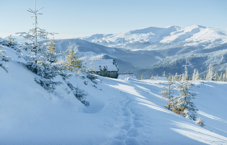 Cabin in the mountains in winter. Mysterious fog. In anticipatio