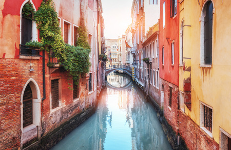 Traditional Gondolas on narrow canal between colorful historic houses in Venice Italy