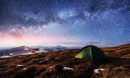 the starry sky above the tent in the mountains. Magic event in f Stock Photo