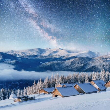 chalets in the mountains at night under the stars. Stock Photo