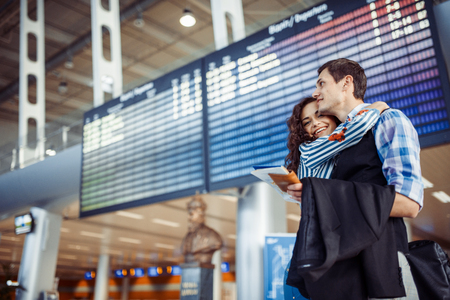 Young loving couple hugging in the airport terminal.
