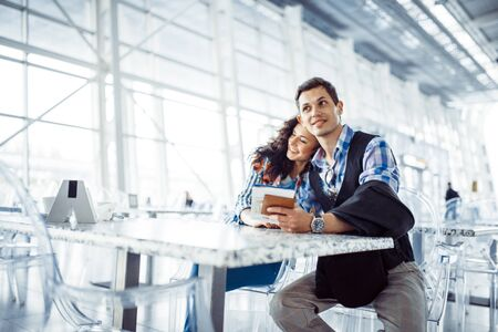 beautiful girl with a guy at the airport in the expected aircraft