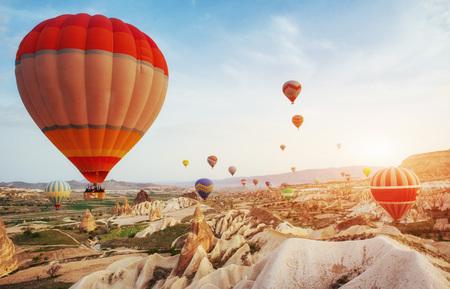 Hete luchtballon die over rotslandschap vliegt in Turkije. Cappadocië met zijn vallei, ravijn, heuvels, gelegen tussen de vulkanische bergen in het Goreme National Park. Stockfoto - 74114011