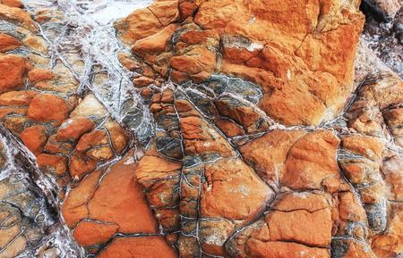赤い石のテクスチャ背景のクローズ アップ。トルコの海の岩の海岸 写真素材