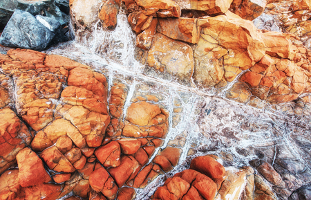 Closeup of a red stone texture background. Rocky coast of the sea in the Turkey