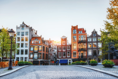 Amsterdam is the capital and most populous city in Netherlands. Scenic houses at sunset