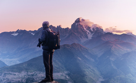 Professional photographer takes photos with big camera on peak of rock. Dreamy majestic landscape, sunset color
