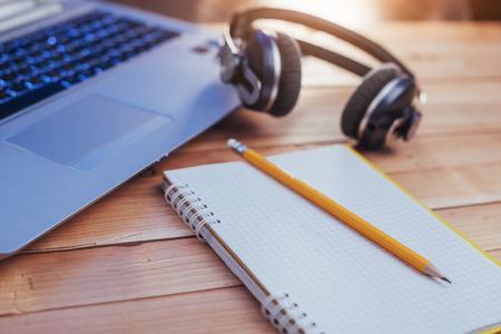 Laptop notitieboekjekoptelefoons en olivchem op een lichte houten achtergrond Stockfoto