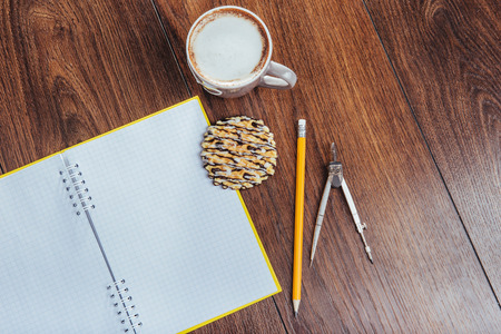 Top view of notebook, stationery, drawing tools and a few cups of coffee